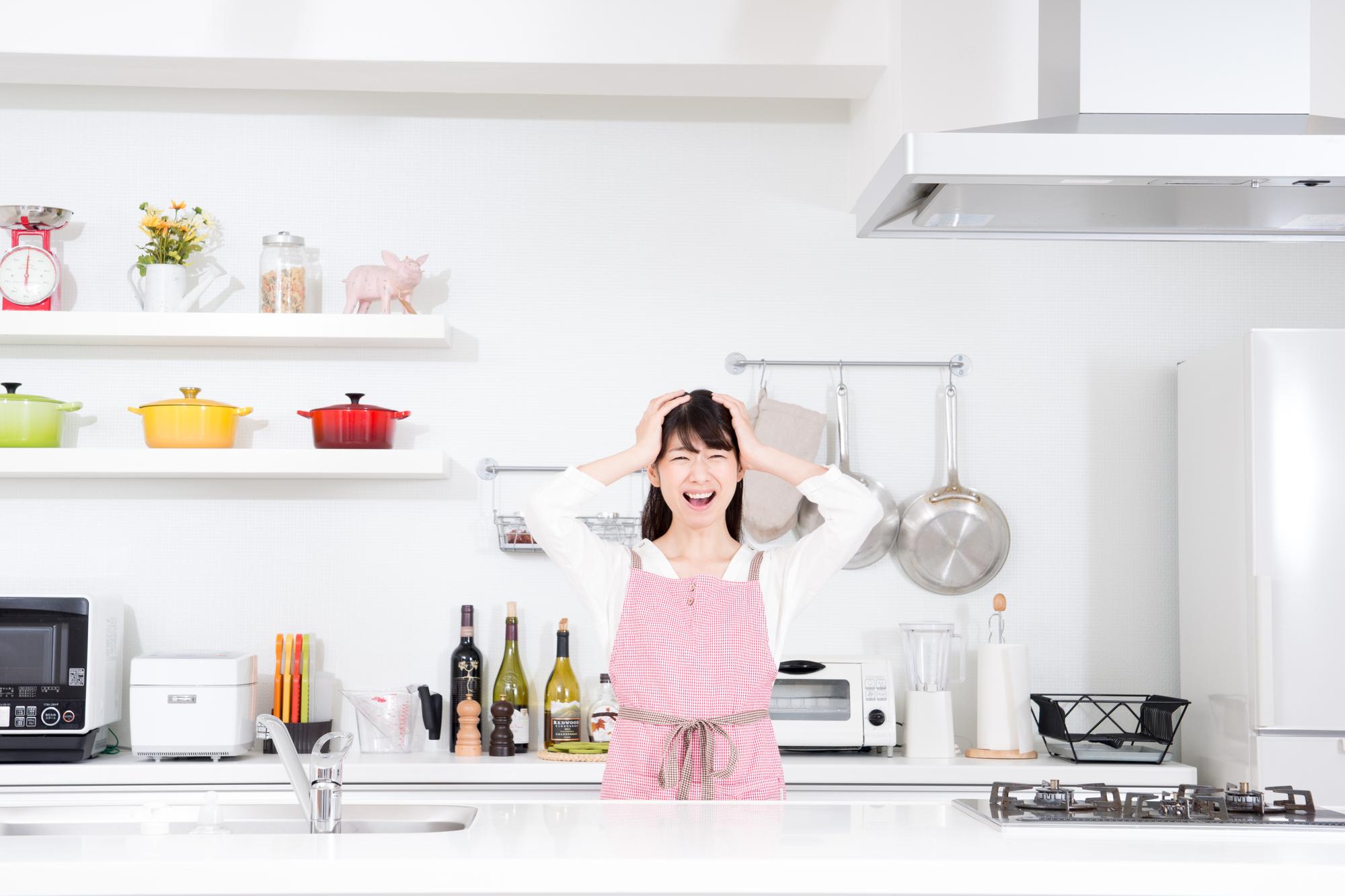キッチンで困って頭を抱える女性